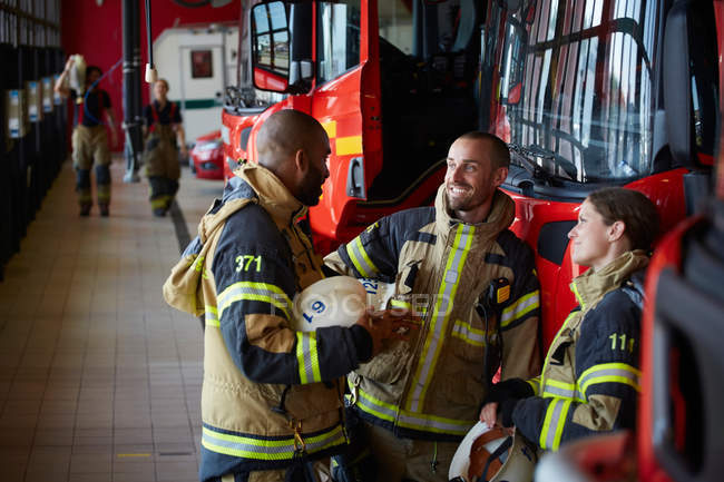 Firefighters in uniform talking while standing at fire station — Stock Photo