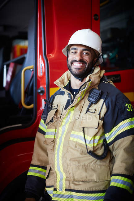 Portrait of smiling male firefighter standing against fire engine at fire station — Stock Photo