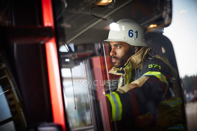 Confident firefighter looking away while sitting in fire engine — Stock Photo