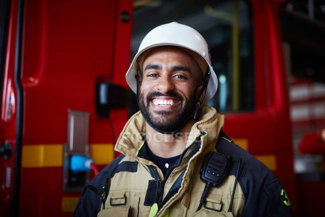 Portrait of smiling firefighter wearing helmet standing at fire station — Stock Photo