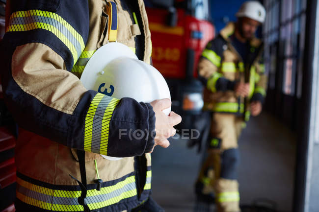 Midsection of female firefighter with protective helmet standing at fire station — Stock Photo