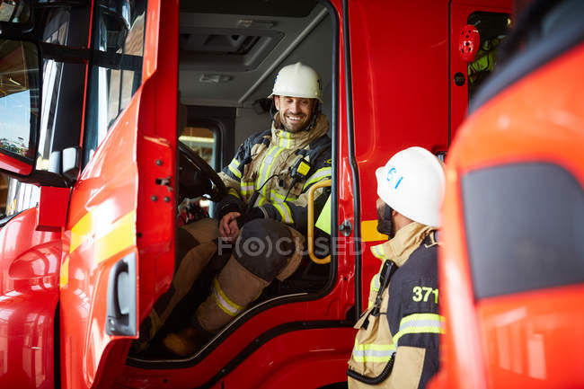 Firefighter talking with coworker while sitting in fire truck at fire station — Stock Photo