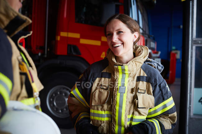 Sorrindo bombeiro feminino olhando para o colega de trabalho enquanto se comunica na estação de incêndio — Fotografia de Stock