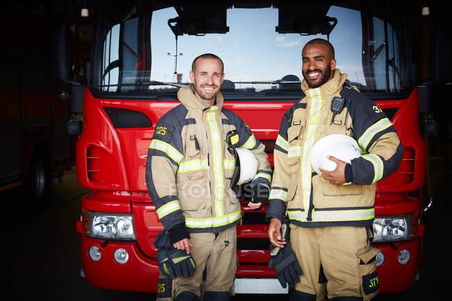 Retrato de colegas de trabalho em pé na frente do motor de incêndio na estação de incêndio — Fotografia de Stock
