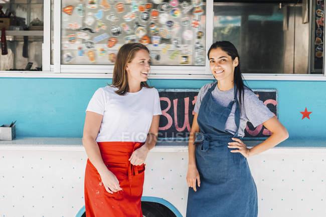 Confiants jeunes propriétaires multi-ethniques femmes debout contre camion alimentaire — Photo de stock