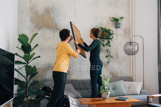 Mid adult man passing picture frame to girlfriend against wall in living room at new home — Stock Photo