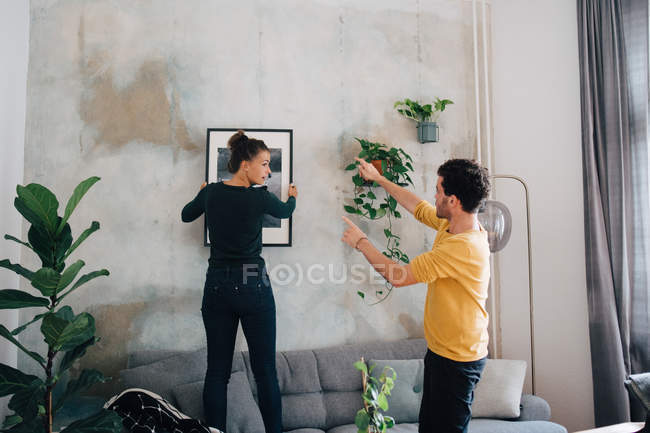 Boyfriend guiding girlfriend in hanging picture frame on wall at new home — Stock Photo