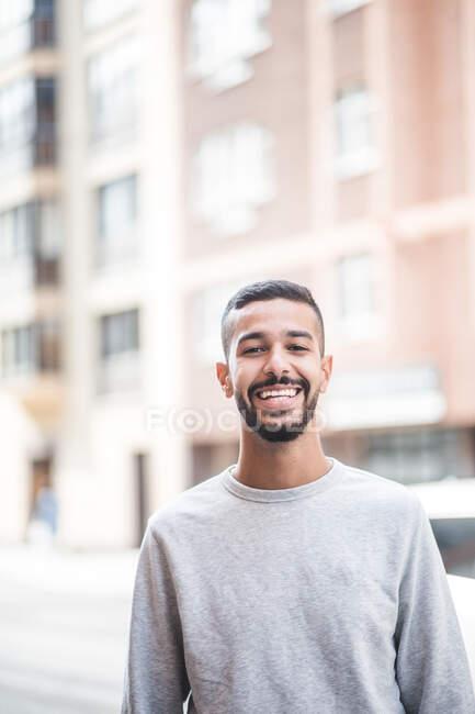 Ritratto di giovane uomo sorridente in piedi all'aperto — Foto stock