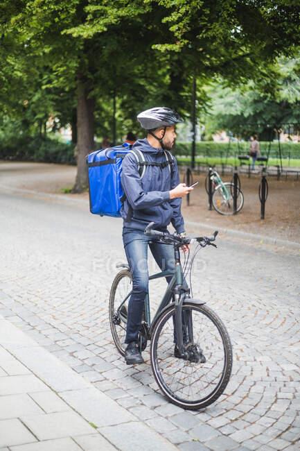 Comprimento total do homem de entrega de alimentos em bicicleta na rua — Fotografia de Stock