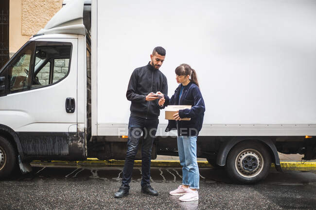 Young woman signing on smart phone while receiving package from male mover — Stock Photo