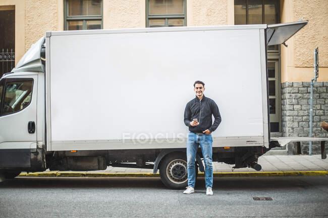 Portrait d'un homme se tenant debout contre un camion dans la rue en ville — Photo de stock