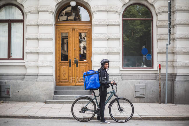 Side view portrait of smiling delivery woman with bicycle on street in city — Stock Photo