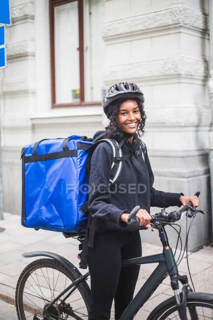 Ritratto di donna sorridente con bicicletta in città — Foto stock