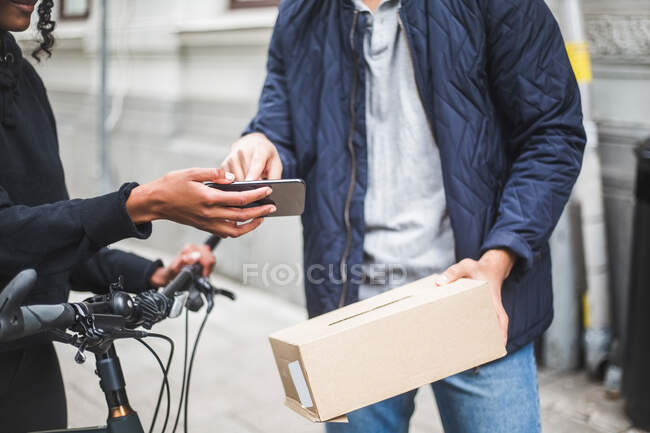 Midsection of delivery woman taking sign from male customer while delivering package on sidewalk in city. - foto de stock