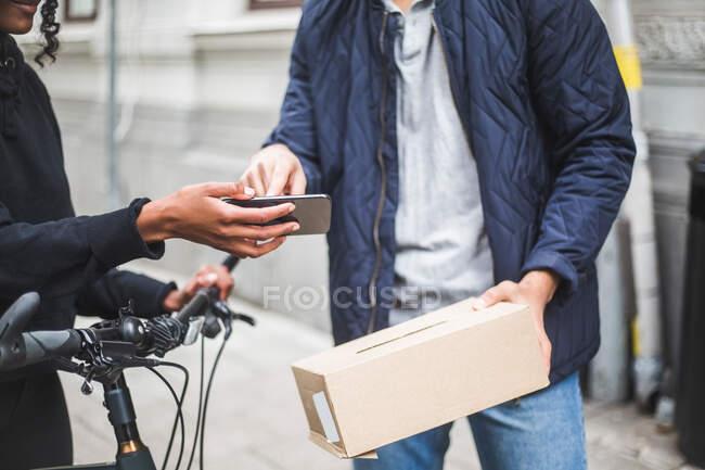 Midsection della donna di consegna prendendo segno dal cliente maschile mentre consegna pacchetto sul marciapiede in città — Foto stock