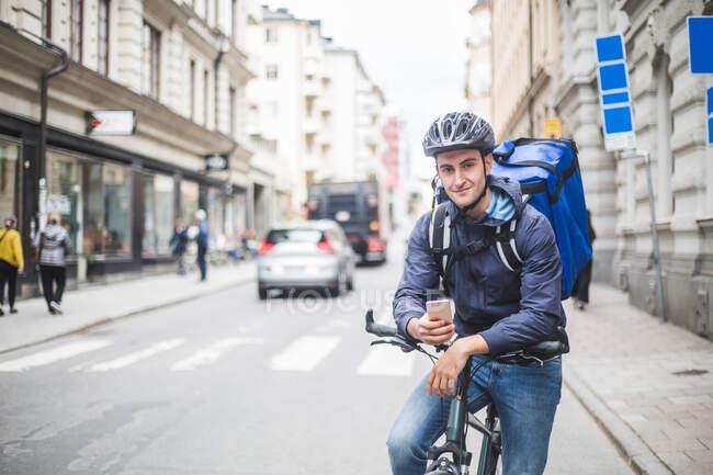 Porträt eines selbstbewussten Essenslieferanten mit Fahrrad auf der Straße in der Stadt — Stockfoto