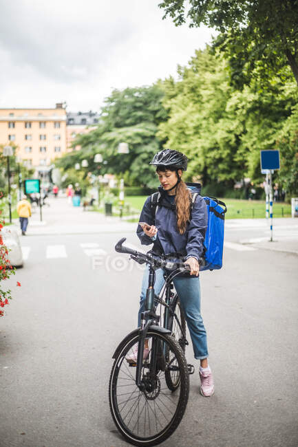 Food delivery woman using mobile phone at street in city — Stock Photo