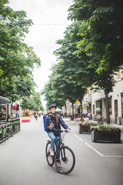 Mulher entrega de alimentos com bicicleta na rua na cidade — Fotografia de Stock