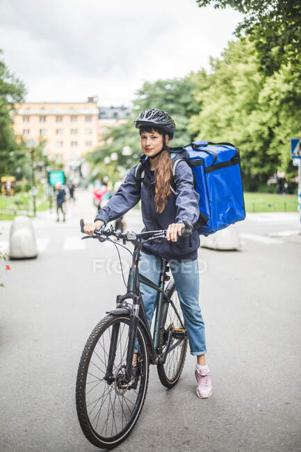 Portrait of confident food delivery woman with bicycle on street in city — Stock Photo