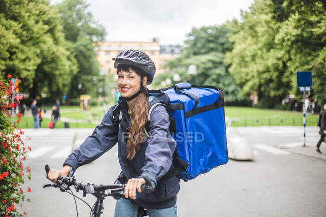 Portrait of smiling food delivery woman with bicycle on street in city — Stock Photo