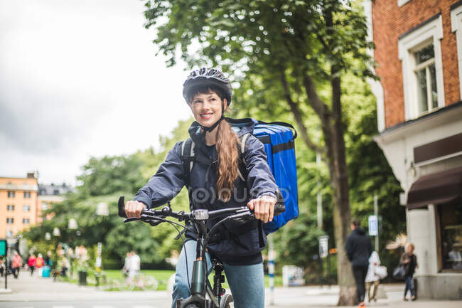 Smiling food delivery woman with bike on street in city. - foto de stock