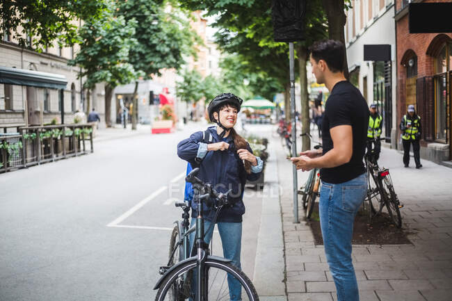 Delivery woman talking with male customer standing on sidewalk in city — Stock Photo