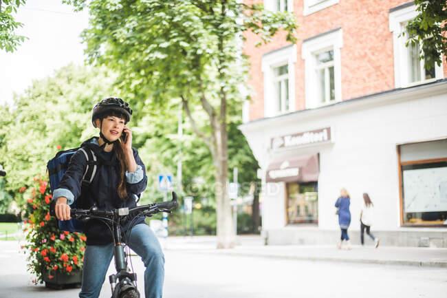Mulher entrega de alimentos falando em telefone inteligente na rua na cidade — Fotografia de Stock