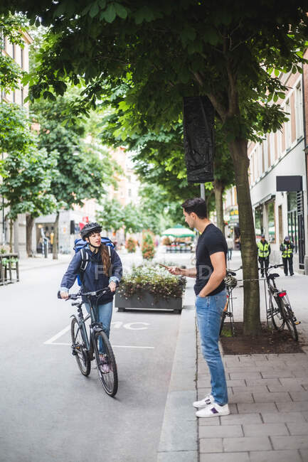 Delivery woman talking with male customer standing on sidewalk — Stock Photo