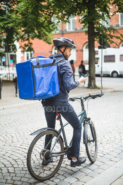 Homem entrega de alimentos com bicicleta usando telefone inteligente na rua na cidade — Fotografia de Stock