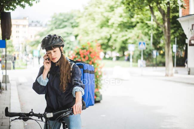 Mulher entrega de alimentos falando no telefone celular na rua na cidade — Fotografia de Stock