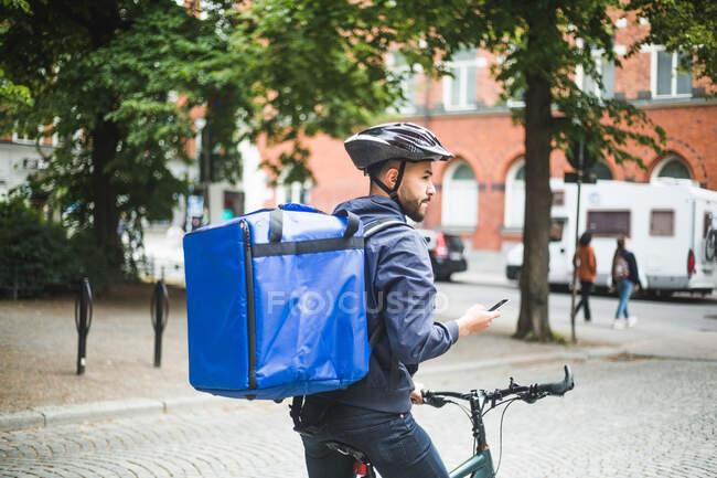 Homem entrega de alimentos com bicicleta olhando para longe enquanto está na rua na cidade — Fotografia de Stock
