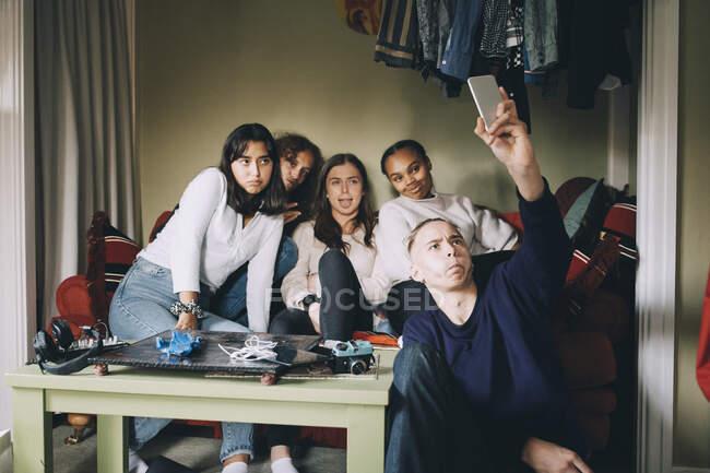 Amigos tomando selfie no telefone inteligente, enquanto faz rostos na sala de estar em casa — Fotografia de Stock
