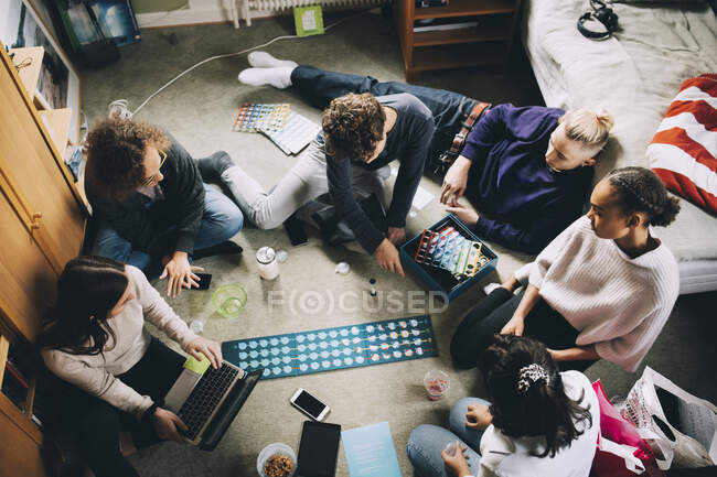 High angle view of teenage girls and boys playing board game in bedroom — Stock Photo