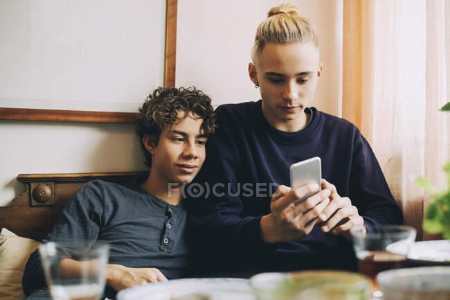 Adolescentes usando telefone celular enquanto descansa no sofá em casa — Fotografia de Stock