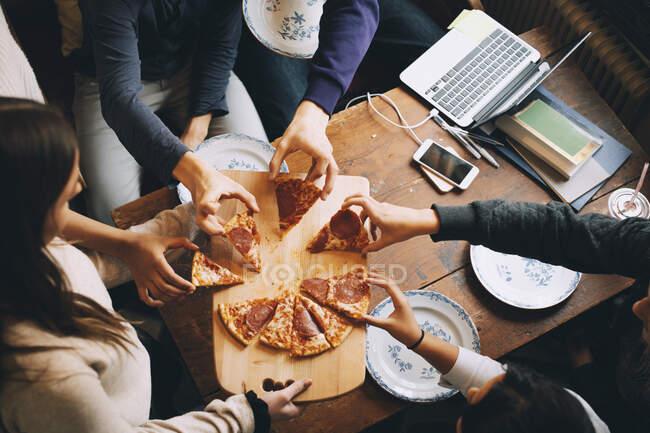 Высокоугольный вид друзей, принимающих кусочки пиццы за обеденным столом — стоковое фото