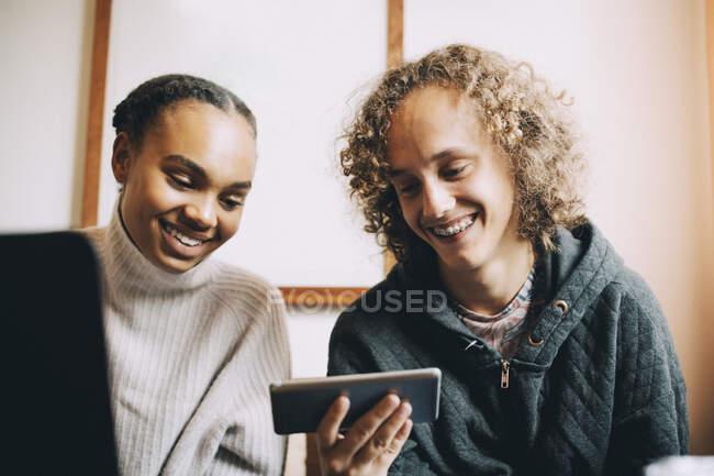 Adolescentes machos e fêmeas sorrindo ao olhar para o telefone inteligente no quarto — Fotografia de Stock