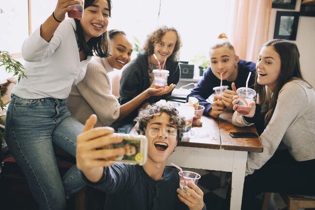 Teenage boy taking selfie with friends on smart phone while drinking smoothie at home — Stock Photo
