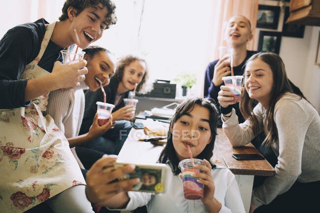 Teenage girl taking selfie with friends through mobile phone while enjoying smoothie at home — Stock Photo