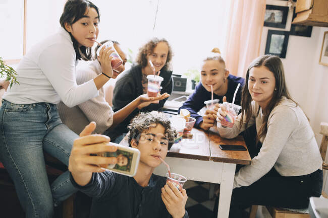 Teenage boy taking selfie with friends through mobile phone while enjoying smoothie at home — Stock Photo