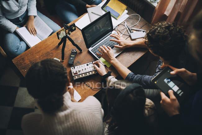 Vue à angle droit d'amis adolescents faisant leurs devoirs en utilisant un ordinateur portatif et un mélangeur de sons à la maison — Photo de stock