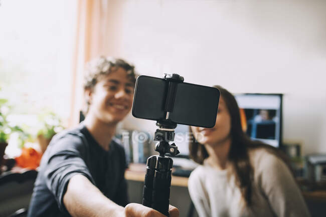 Teenage friends taking selfie with smart phone on monopod while sitting at home — Stock Photo