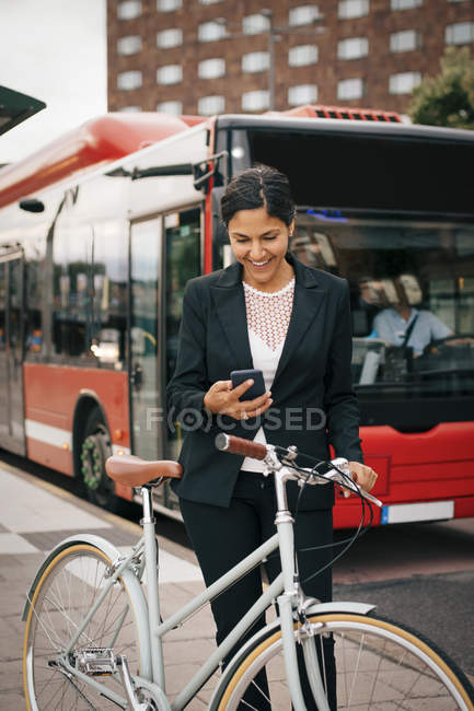 Smiling business woman using smart phone while standing with bike against bus on street in city. - foto de stock