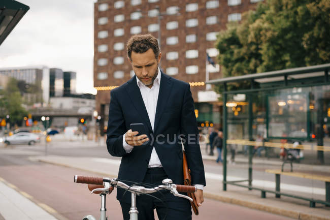 Businessman using mobile phone while standing with bicycle on street in city — Stock Photo