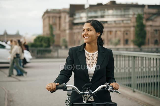 Mujer de negocios sonriente con bicicleta en puente en la ciudad - foto de stock