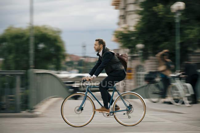 Багатокілометровий впевнений бізнесмен їздить на велосипеді по мосту. — стокове фото
