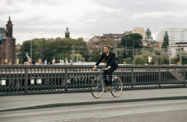 Businessman riding bicycle on street in city against sky — Stock Photo