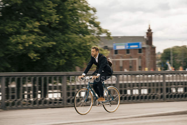 Full length of confident businessman riding bicycle on city street — Stock Photo