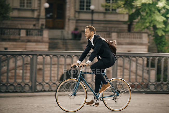 Full length of businessman cycling on street in city — Stock Photo