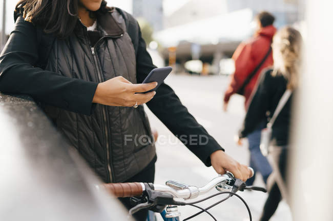 Midsection of business woman using smart phone while standing with bike in city. - foto de stock