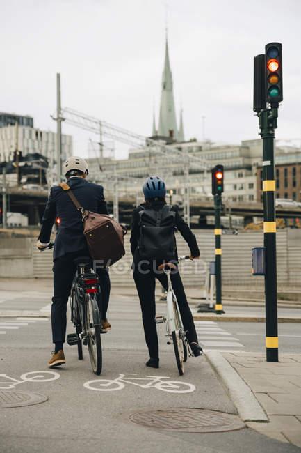 Visão traseira do empresário e empresária com bicicletas na rua da cidade — Fotografia de Stock